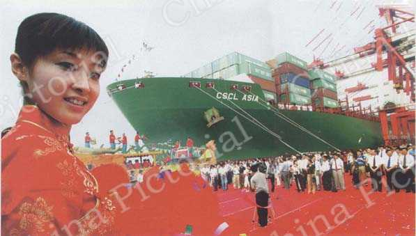 A ceremony participant waits for a ship to launch in Shanghai on July 9, 2004. This liner, capable of carrying 8,500 TEU containers, believed to be the largest of its kind in the world, embarked on its maiden voyage from China's financial hub to North America.
