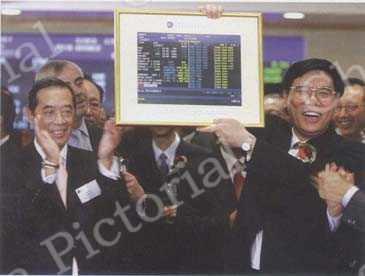 Chairman of the Industrial and Commercial Bank of China (ICBC) Jiang Jianqing (right) holds a photo of the opening share price of ICBC, presented by Hong Kong Exchange Chairman Ronald Arculli (left), during a ceremony marking ICBC's trading debut at the Hong Kong Stock Exchange on October 27, 2006. by Paul Yeung