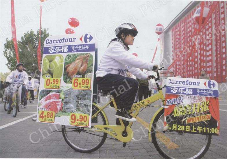 Staff prepare to hit the streets on their bicycles to advertise the French retail giant Carrefour's Tongzhou store in Beijing on October 28, 2006. Carrefour currently operates 77 supermarkets in China, and plans to open another 12 in 2006.